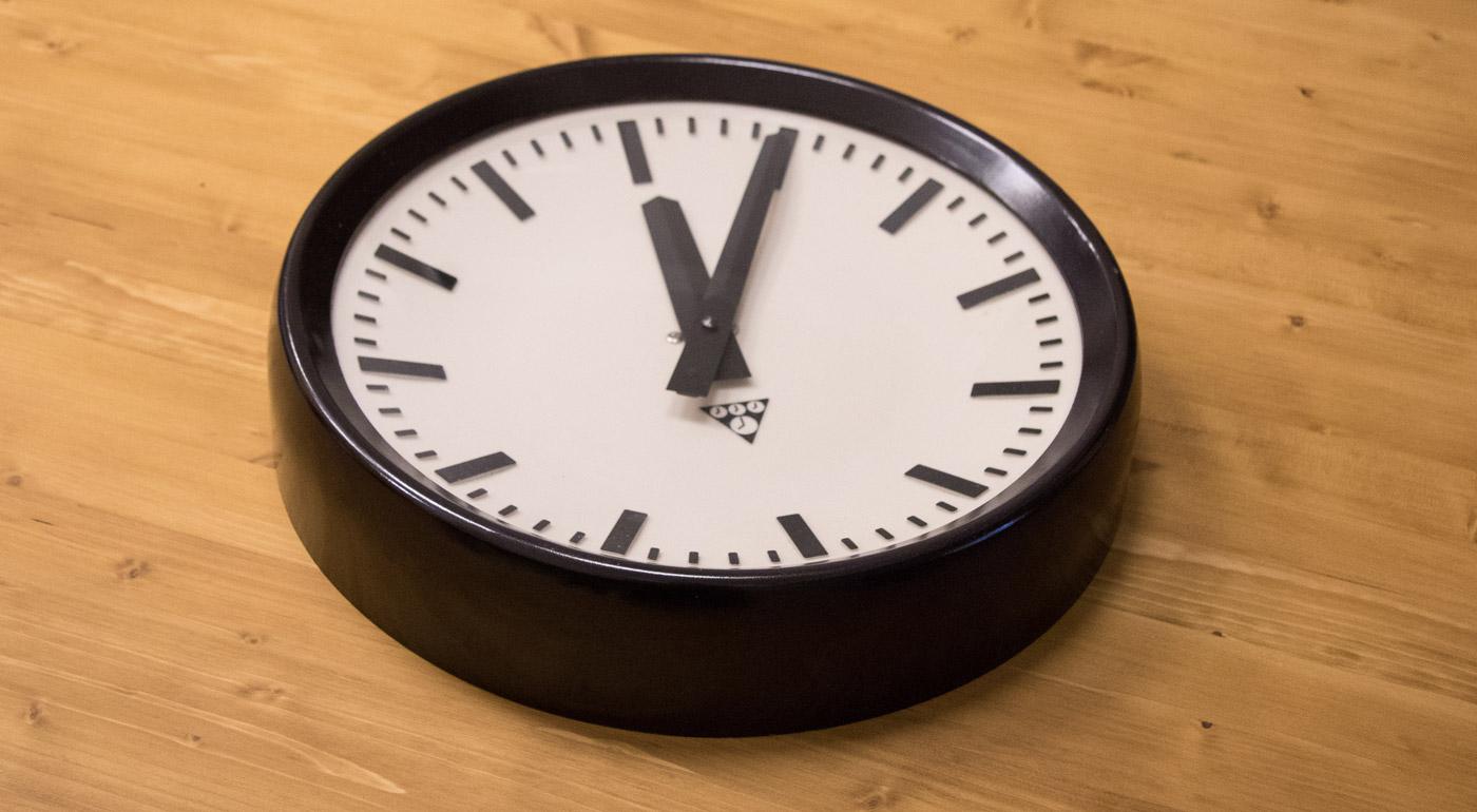 Nástenné hodiny Pragotron P273n zo 70. rokov. Materiál bakelit, plast a sklo.